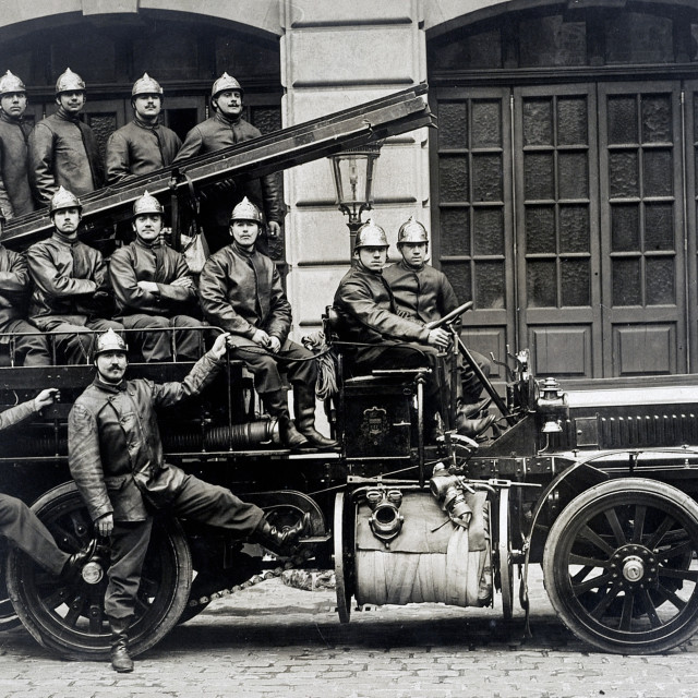 """""""old postcard of a group of firemen on a truck"""" stock image"""