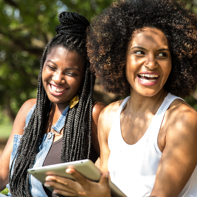 """Brazilian women using tablet computer in the park"" stock image"