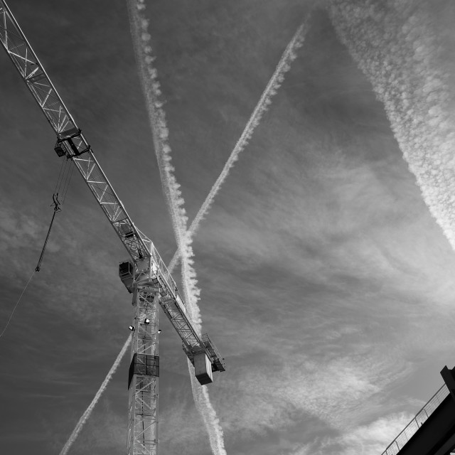 """Crane on a construction site with jet trails and clouds in the sky behind"" stock image"