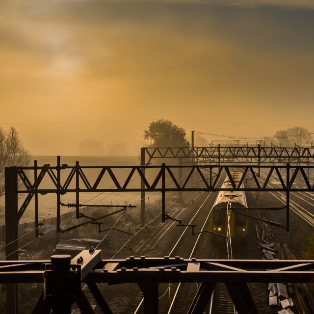 """Morning express train passing along the tracks on a misty morning"" stock image"
