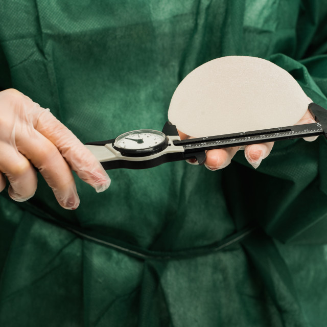 """Plastic surgeon hands measuring silicon breast implants with calliper"" stock image"