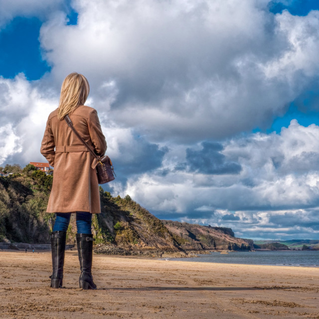 """Blonde woman at the seaside looking out to se."" stock image"