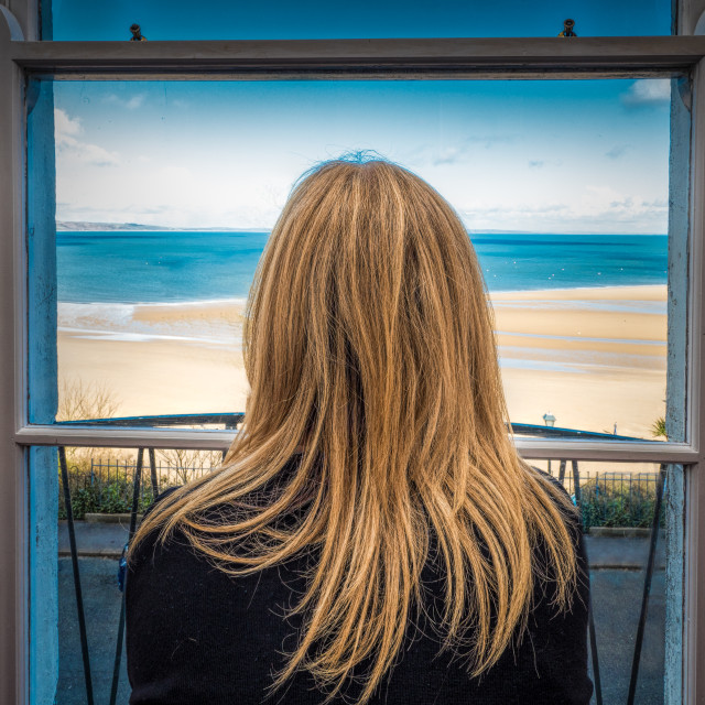 """Blonde woman staring through window at the sea."" stock image"