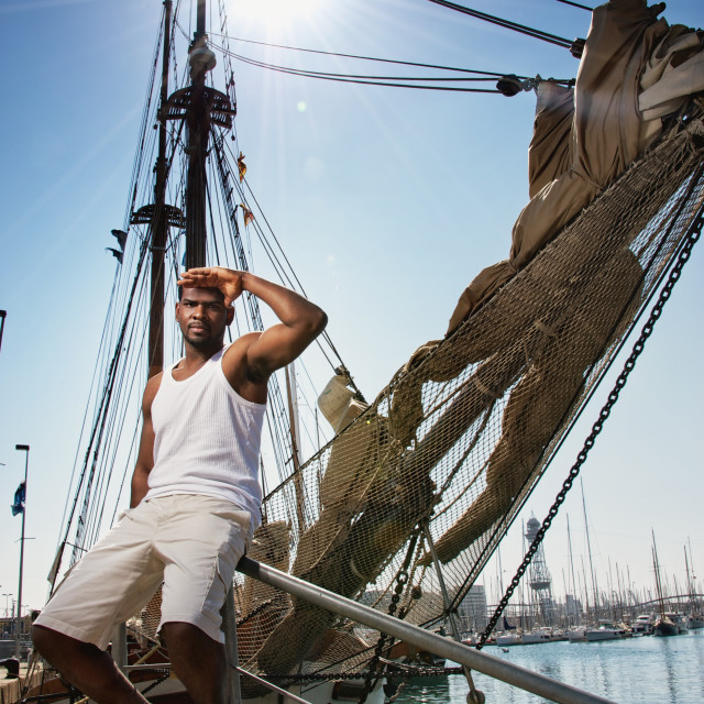 """""""Handsome afro-american man against boat in port."""" stock image"""