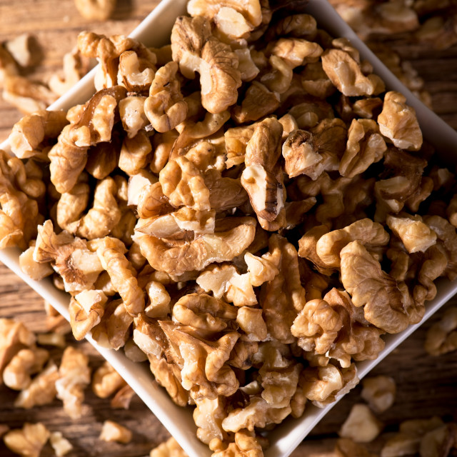 """""""White bowl on wooden board full of walnuts"""" stock image"""