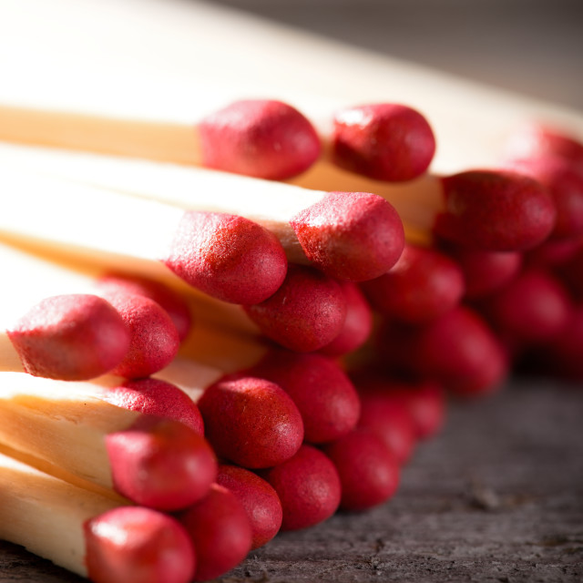 """Heap of matchsticks with red heads on wooden board"" stock image"