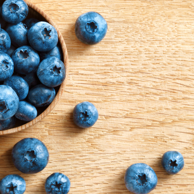 """Healthy blueberries in bowl on wooden background."" stock image"
