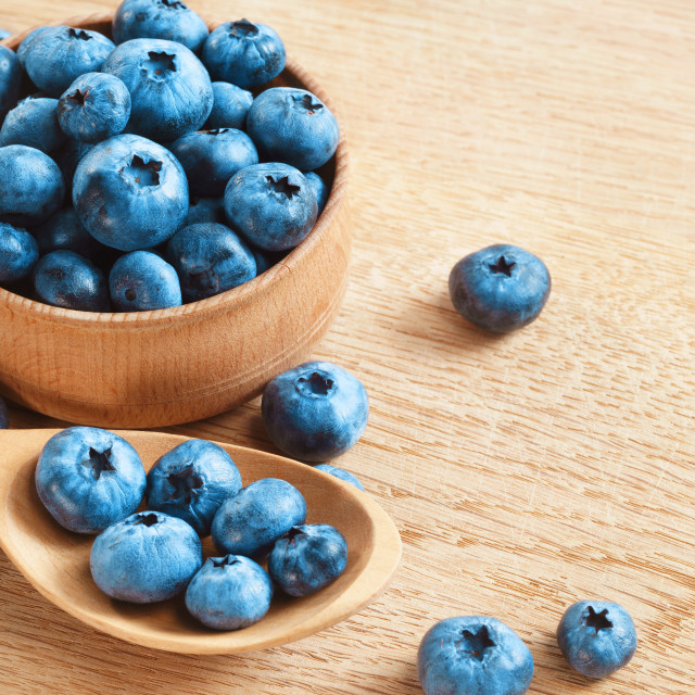 """Organic blueberries in bowl on wooden background."" stock image"