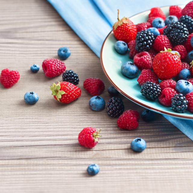 """Ceramic plate of assortment berries blueberries, strawberries, raspberries, blackberries at old wooden table."" stock image"