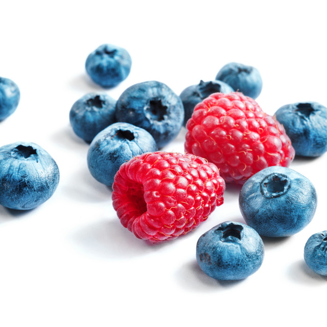 """Blueberries and raspberries on white background."" stock image"