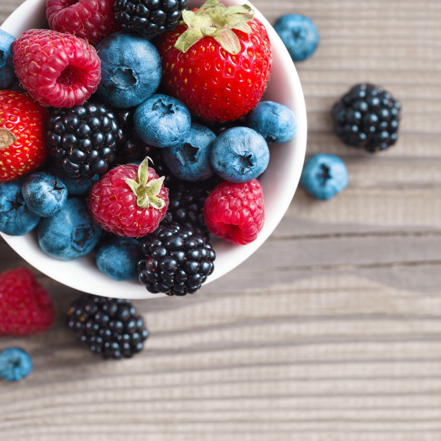 """""""Mix of fresh berries in a basket on rustic wooden background."""" stock image"""