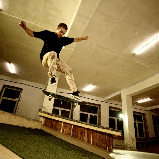 """Young man performing a stunt in a skatepark"" stock image"