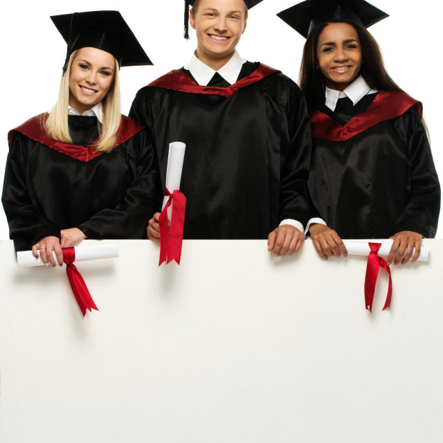 """""""Multi ethnic group of graduated young students with blank notice board"""" stock image"""