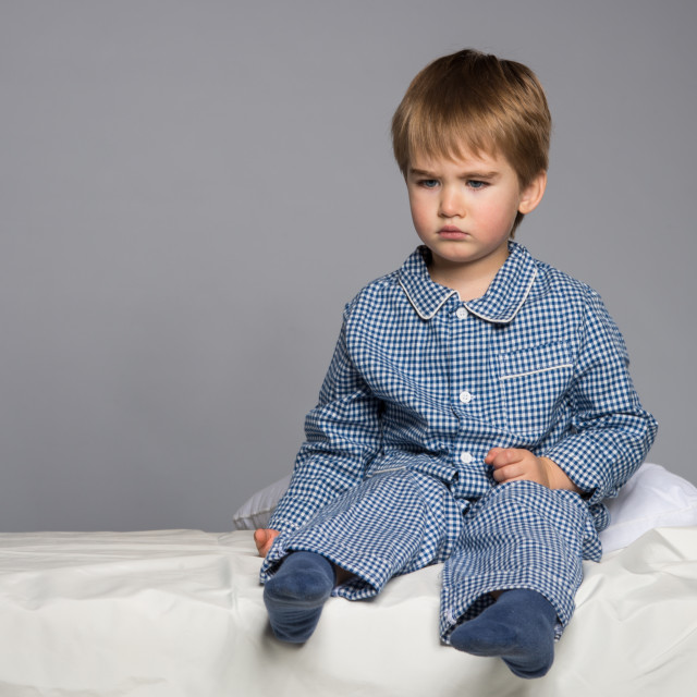"""""""Disappointed little boy in blue pyjamas on bed"""" stock image"""