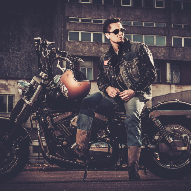 """Biker and his bobber style motorcycle on a city streets"" stock image"