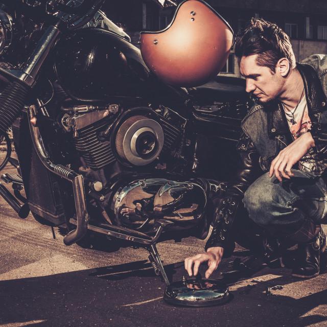 """Biker repairing his custom motorcycle bobber on a road"" stock image"