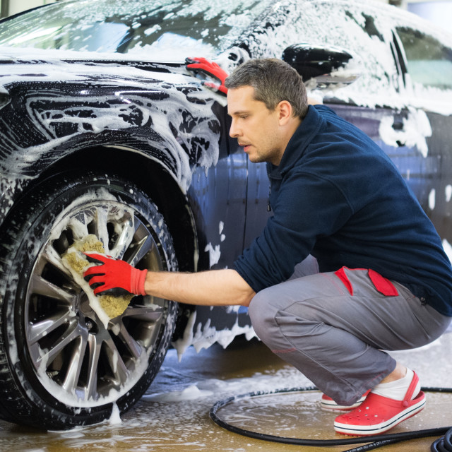 """Man worker washing car's alloy wheels on a car wash"" stock image"