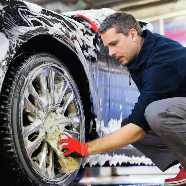 """""""Man worker washing car's alloy wheels on a car wash"""" stock image"""