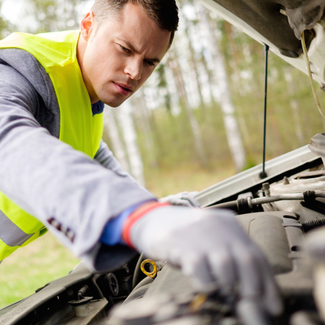 """Man fixing broken car on a roadside"" stock image"