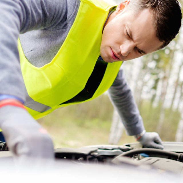 """Man fixing broken car on a roadside"" stock image"