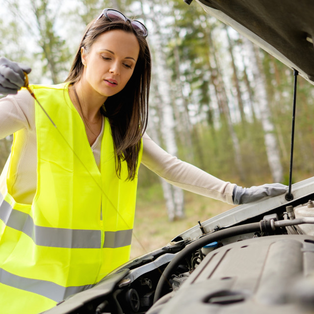 """Woman checking oil level on a roadside"" stock image"
