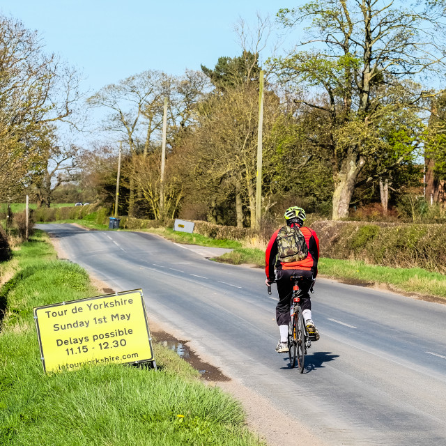 """Tour de Yorkshire 2016 cyclist passes road closure sign on deserted road"" stock image"