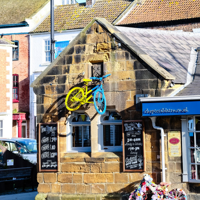 """Tour de Yorkshire 2016 a painted bicycle on the wall of a building in the North Yorkshire town of Stokesley upright"" stock image"
