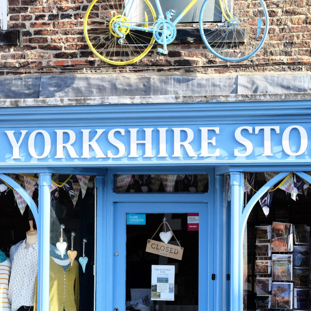 """Tour de Yorkshire 2016 a painted bicycle above the door of The Yorkshire Store in the North Yorkshire town of Stokesley upright 1"" stock image"