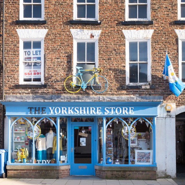 """Tour de Yorkshire 2016 a painted bicycle above the door of The Yorkshire Store in the North Yorkshire town of Stokesley upright 2"" stock image"