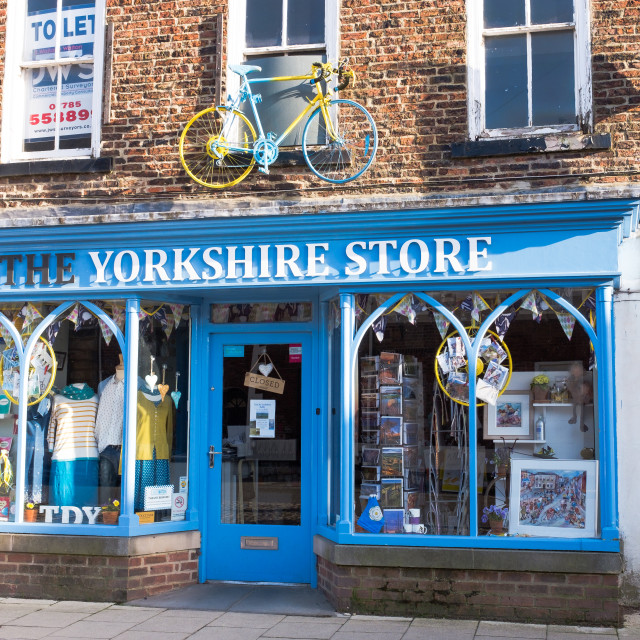 """Tour de Yorkshire 2016 a painted bicycle above the door of The Yorkshire Store in the North Yorkshire town of Stokesley wide"" stock image"