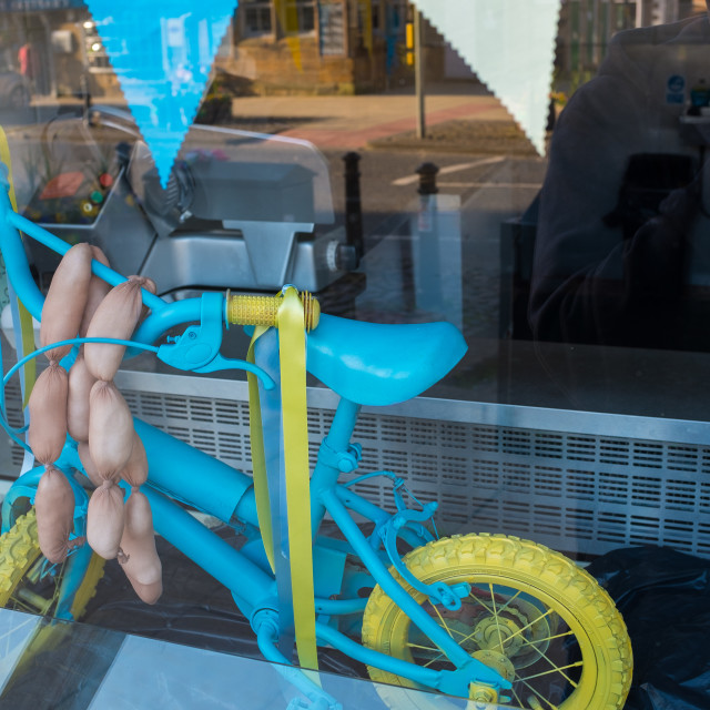 """Tour de Yorkshire 2016 a small painted bicycle with fake sausages hanging from it in a butcher shop window in the North Yorkshire town of Stokesley"" stock image"