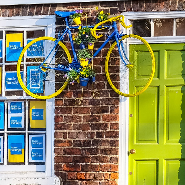 """Tour de Yorkshire 2016 posters in the windows and a painted bicycle above a brightly coloured doorway in the North Yorkshire town of Stokesley"" stock image"