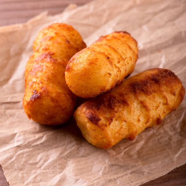 """Three crispy potato croquettes on piece of brown paper"" stock image"
