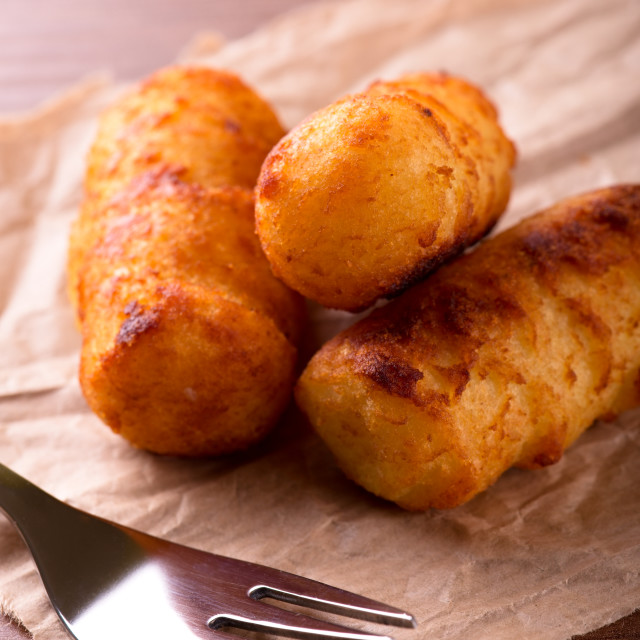 """Fork in front of three fried crispy potato croquettes"" stock image"