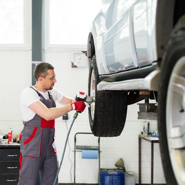 """Serviceman unscrewing wheel in car workshop"" stock image"