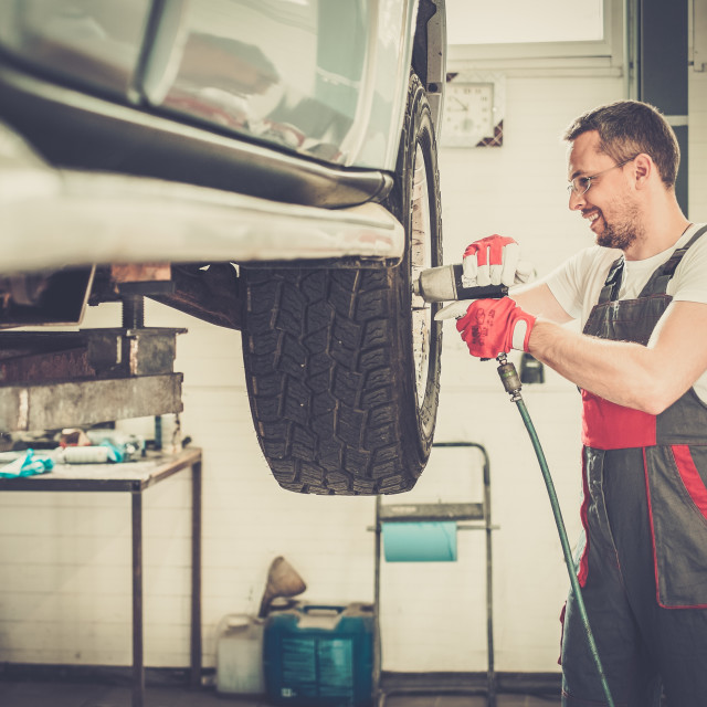 """""""Cheerful serviceman unscrewing wheel in car workshop"""" stock image"""