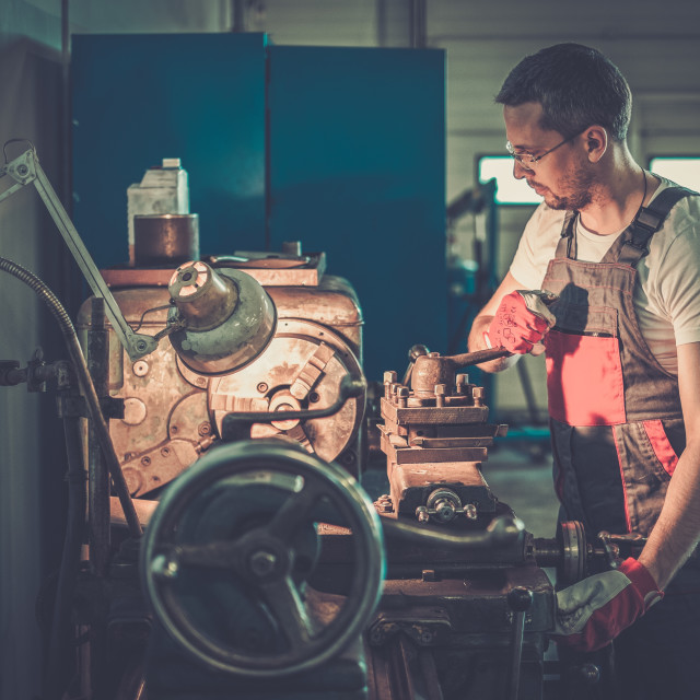 """Serviceman working on lathe machine in car workshop"" stock image"