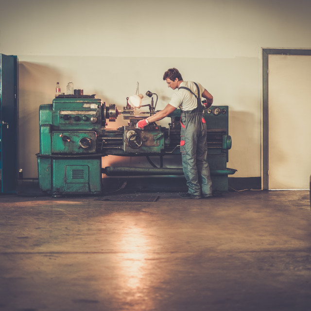 """Serviceman working on turning lathe in car workshop"" stock image"