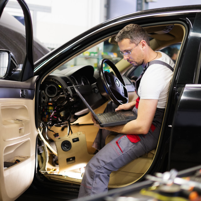 """""""Serviceman making car diagnostics with laptop in a workshop"""" stock image"""