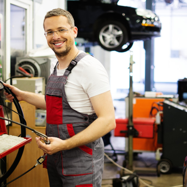 """Serviceman with co/hc diagnostic tool in a car workshop"" stock image"