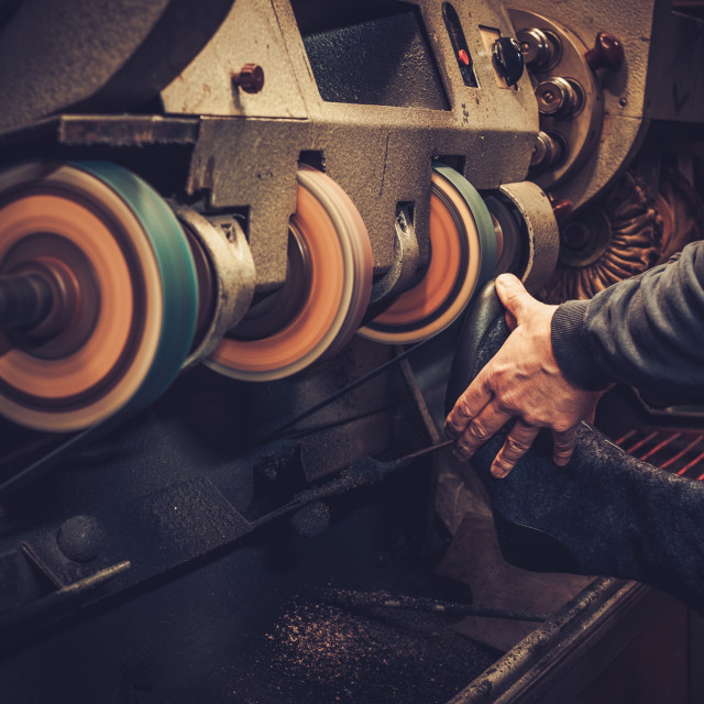 """""""Shoemaker performs shoes in the studio craft grinder machine."""" stock image"""