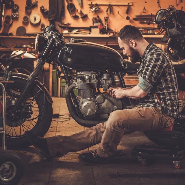 """Mechanic building vintage style cafe-racer motorcycle in custom garage"" stock image"