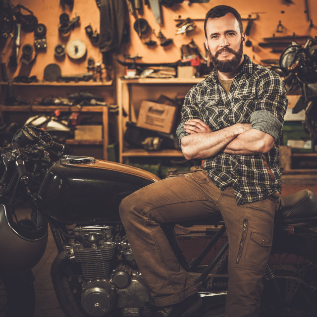 """""""Rider and his vintage style cafe-racer motorcycle in customs garage"""" stock image"""