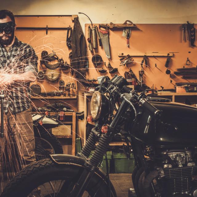 """Mechanic doing lathe works in motorcycle customs garage"" stock image"