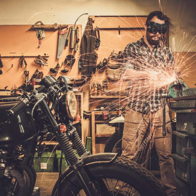 """Mechanic doing lathe works in motorcycle customs garage"" stock image"