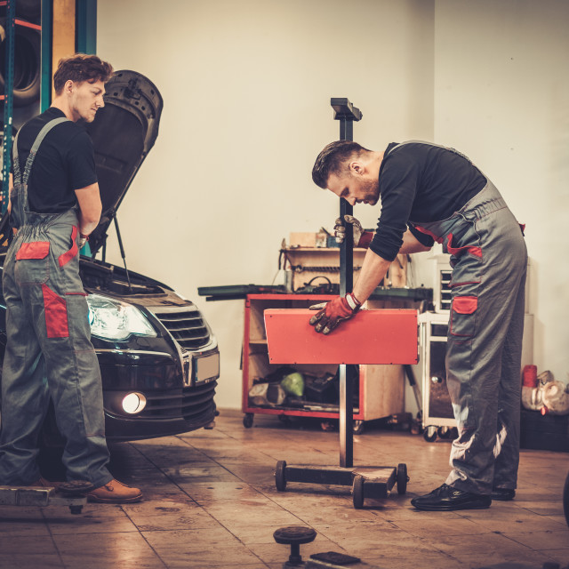 """Professional car mechanics inspecting headlight lamp of automobile in auto..."" stock image"