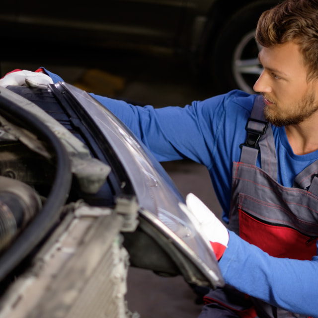 """Mechanic with new car headlight in a workshop"" stock image"
