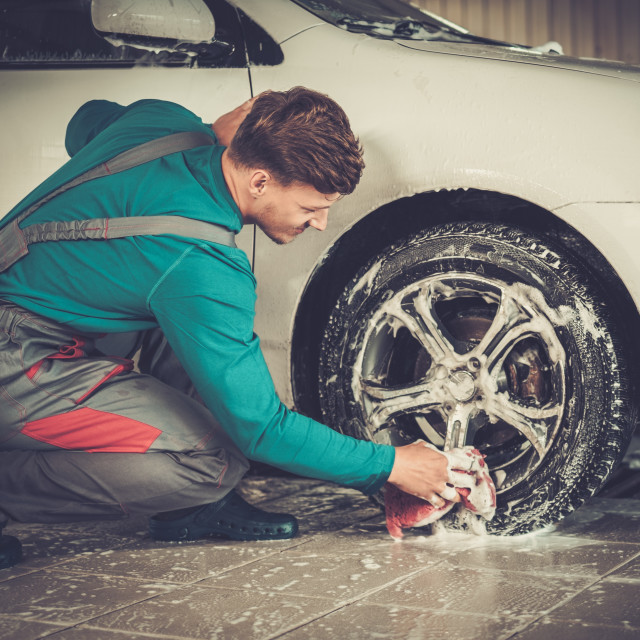 """Man worker washing car's alloy rims on a car wash"" stock image"