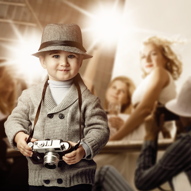 """Baby boy with retro camera over photo shoot background."" stock image"