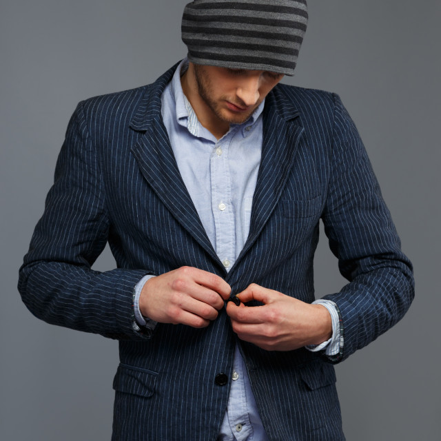 """Stylish young man in jacket and beanie hat"" stock image"